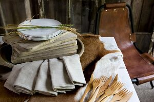 Plates and wooden chopping boards next to ecru linen napkins and wooden cutlery on cow skin on table