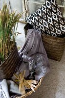 Basket of cereal ears next to wooden cutlery and glasses on lilac fabric and ethnic cushion in wicker basket
