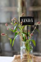 Wild flowers and name tag in vintage glass jar