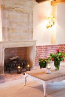Bouquets of roses and lit candle lanterns in front of disused fireplace