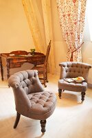 Two upholstered armchairs in front of window with gathered curtain and antique writing desk in hotel room