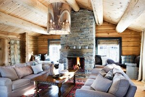 Comfortable sofa set and wooden coffee table below modern, retro ceiling light in log cabin interior with open fireplace