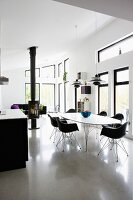Dining area with black shell chairs around white table in open-plan, modern interior