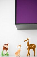 50s-style animal ornaments on shelf below wall-mounted cabinet