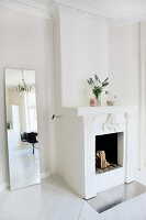 White out - modern full-length mirror next to open fireplace in renovated interior with stucco frieze