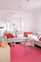 Large, round mirror on wall behind corner sofa and plexiglass table on pink rug
