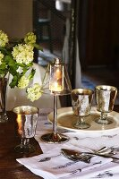 Elegant candle lantern on lamp base next to vintage wine glasses on table