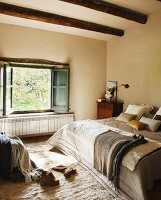 Comfortable bed with blankets and scatter cushions in front of open window in bedroom with wood-beamed ceiling