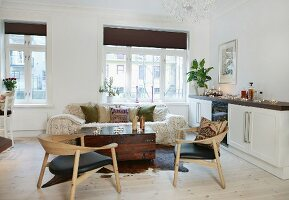 Wooden chairs and trunk-like coffee table next to white sideboard in open-plan interior