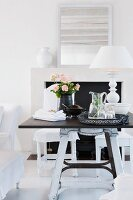 Black and white furnishings - tray of refreshing drinks and table lamp with white lampshade on dark tabletop