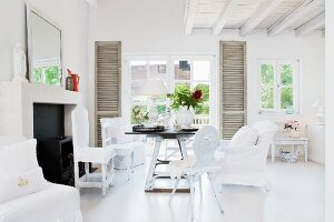 Various chairs around rustic table in front of terrace doors with interior shutters
