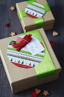 Festive gift boxes decorated with round patterned cards, green ribbons and Father Christmas boot