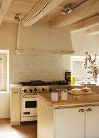 Kitchen island with wooden worksurface in front of cooker with gas hob under extractor hood on wood-beamed ceiling in rustic setting