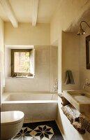 Vintage bathroom with patterned floor tiles in front of bathtub below window