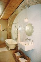 Washbasin and free-standing bathtub in rustic bathroom of Spanish country house