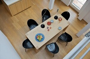 View down onto modern dining table with black shell chairs on wooden floor