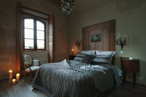 Double bed with modern, stone grey bedspread contrasting with wood-panelled headboard, small items of antique furniture and Rococo-style sconce lamps