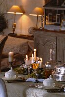 Festively set table in candlelight atmosphere and table lamps on shelf in background