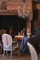 Lit candles in chandelier above small Rococo chair and table draped in table cloth in front of rustic fireplace in living room