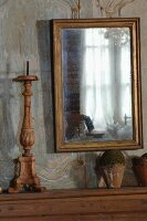Gilt-framed mirror on faded wood-panelled wall and wooden candlestick next to vintage terracotta pots on console table