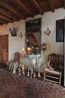 Rustic hallway in French country house with antique candlesticks on floor in front of Rococo console table