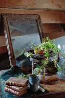 Old cabinet decorated with antique, patinated collectors' items and ivy planted in old amphora