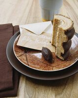 A slice of Baumkuchen (German layer cake) and an envelope with writing on it, on a dish with a reticulated design
