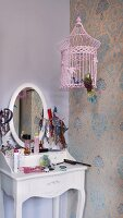 Romantic girls' dressing table and pink bird cage against wallpaper with traditional pattern