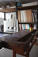 Old workbench in front of shelves of wooden elements in attic workshop