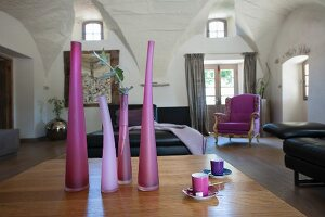 Vases in various shades of purple on table and black leather sofa in spacious living room with vaulted ceiling