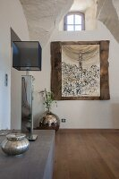 Table lamp with cubic fabric lampshade on half-height cabinet opposite wall with picture in rustic wooden frame in foyer