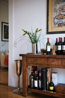 A rustic dresser with an assortment of bottles of wine and spirits