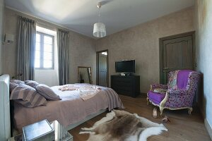 Simple bedroom with bed in front of window and Rococo-style reading chair with colourful upholstery