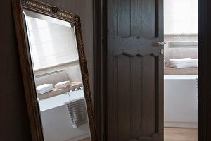 Gilt-framed mirror next to open interior door with view into bathroom