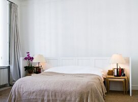 Double bed with pale brown cover in front of white, half-height wooden panel in minimalist bedroom