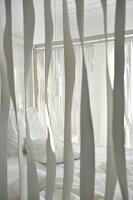View through ribbons hanging from wooden frame of four-poster bed with white bedlinen