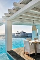 Set table and chairs with white loose covers on roofed wooden terrace next to pool with view of yacht on ocean