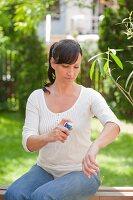 Frau besprüht ihren Arm mit einem Spray