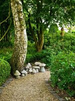 Gravel path & stone mushroom ornaments in garden