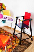 Retro-style dining room with high chair, colourful plastic chairs & long-pile rug