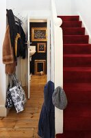 Red carpet on staircase in traditional stairwell with open door showing view of gilt picture frames in bathroom
