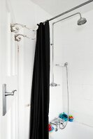 Vintage hooks on door and open, black shower curtain in front of bathtub with shower head on wall