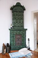 Blanket and cushions on wooden floor in front of green-tiled corner stove with vintage hearth equipment