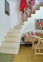 Women's legs on concrete staircase in interior with wooden chair and bench
