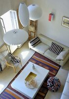 View down onto group of white pendant lamps and modern, cubic coffee table on striped rug in front of sofa