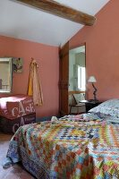 Double bed with colourful, checked bedspread in pink-painted, attic bedroom