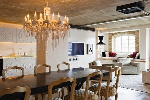 Long dining table and vintage chairs below chandelier in loft-style interior with exposed concrete ceiling