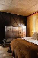 View across bed of vintage metal cupboard on castors against wood-panelled wall and chain curtain in bedroom