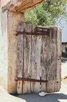 Old wooden cemetery gate in the adobe wall at Mission San Miguel Archangel in San Miguel