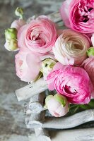 Pink and white ranunculus in basket of white twigs